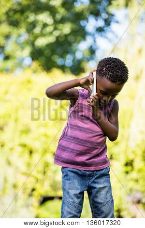 A child is having phone call in a park