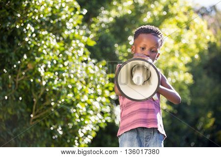 Boy using a megaphone in a park