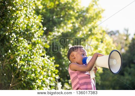 Boy shouting through megaphone in a park