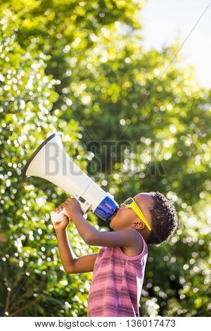 Boy shouting trough megaphone in a park