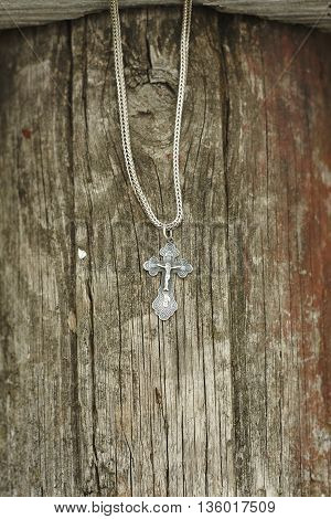 orthodox silver cross on chain on old lumber