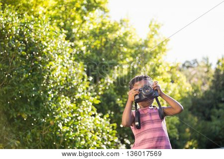 Boyis taking pictures in a park