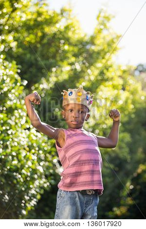 Boy putting arms up with crown in a park