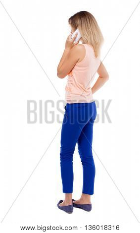 back view of woman talking on the phone.  backside view of person. Rear view people collection. Isolated over white background. Blonde in blue pants makes talking on the phone resting his hand on side