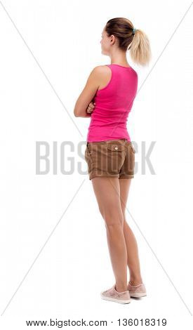 back view of standing young beautiful  woman. girl  watching. Rear view people collection.  backside view of person. Isolated over white background. Blonde in brown shorts stands with his arms folded.