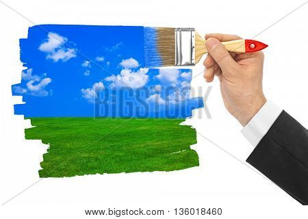 Hand with paintbrush drawing landscape isolated on white background