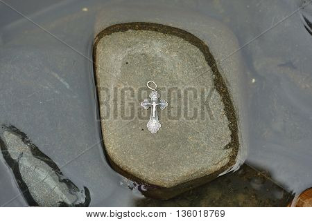 orthodox silver cross on stone in water close up