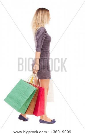 back view of going  woman  with shopping bags . beautiful brunette girl in motion.  backside view of person.  Isolated over white background. girl in the purple dress is left with bags