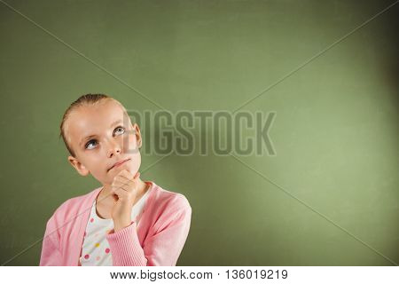 Girl touching her chin on green background
