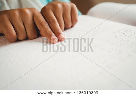 Girl using braille to read at school