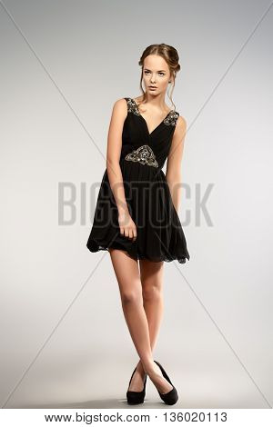 Full length portrait of a pretty young woman in little black dress. Beauty, fashion. Studio shot.