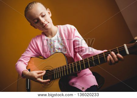 Girl playing the guitar on yellow background
