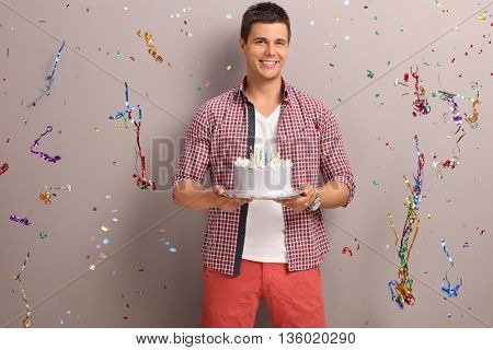 Joyful guy holding a birthday cake with confetti streamers flying around him