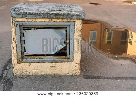 old construction for ventilation in the yard against a puddle with reflection of a fragment of the house