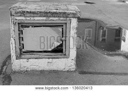 old construction for ventilation in the yard against a puddle with reflection of a fragment of the house of monochrome tone of gray color