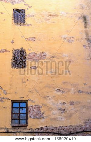 the old big plastered brick wall with windows for ancient background