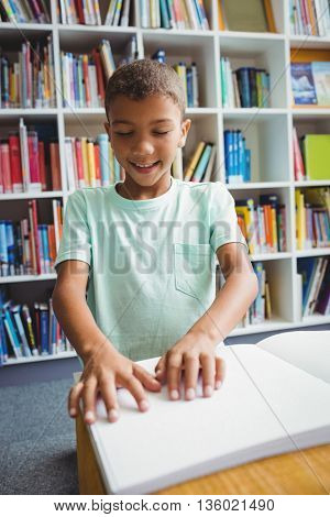 Boy using braille to read in the library