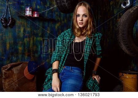Portrait of a modern teenager girl wearing street clothes sitting in the old garage. Grunge style.