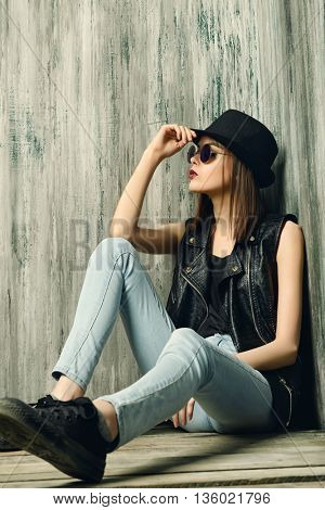 Fashion shot of a modern brunette girl with beautiful big brown eyes wearing jeans and black leather jacket. Beauty, fashion. Youth generation.