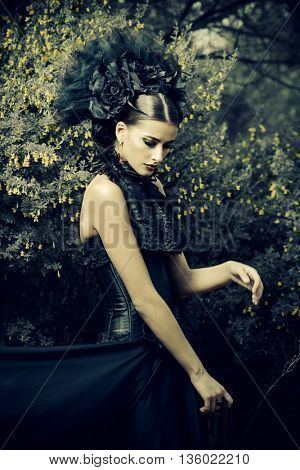 Gothic brunette woman in long black dress and beautiful black headwear posing in the blossoming garden. Medieval, old times. Fashion. Gothic style.