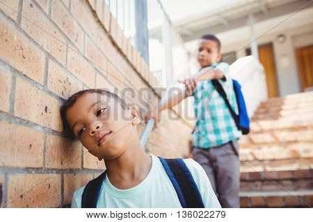 Boy pointing on another boy outside the school