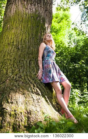 Young teen girl standing near a huge tree