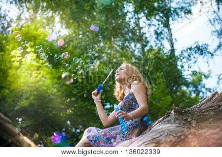 Young girl sitting on a tree in a park playing with soap bubbles