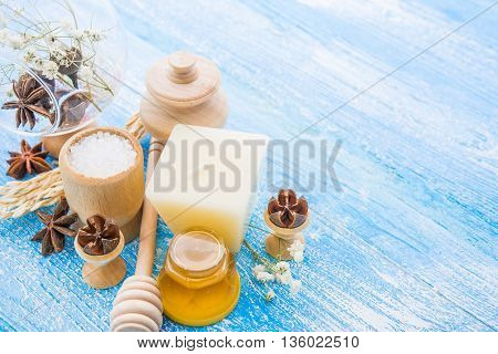 spa treatment -  star anise, honey, salt, arranged with soap bar, pebbles and towels on wood