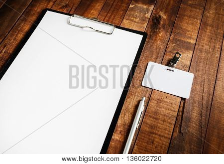Photo of blank letterhead badge and pen on vintage wooden table background. Blank ID template. Branding mock-up for your design.