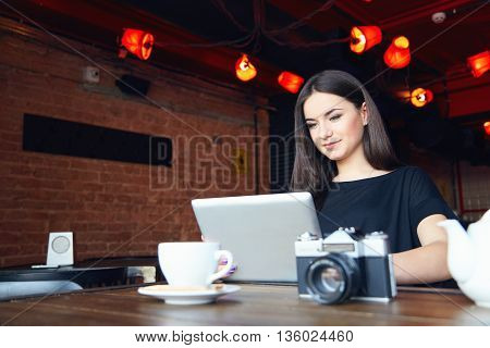 Young attractive student girl in black t-shirt with cute smile working on laptop while sitting alone in coffee shop during free time. Female bloger freelancer photographer. Lifestyle leisure time