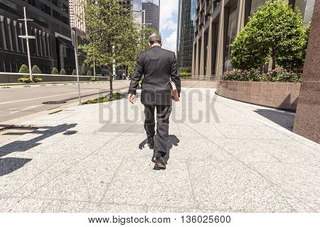 HOUSTON USA - APR 14: Businessman in a black suit walking on the sidewalk in Houston downtown district. April 14 2016 in Houston Texas United States