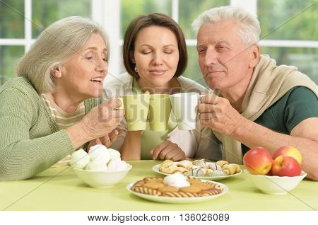 Cute family portrait , adult daughter with senior parents drinkig tea