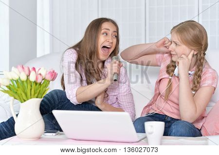 portrait of mother and daughter  with  microphones and  laptop