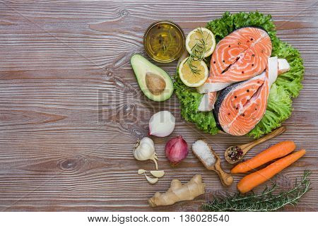 Right salmon fillets on lettuce near carrot avocado onion rosemary lemons garlic ginger spices salt olive oil left empty space on wood background. Salmon fillets and vegetables. Top view.