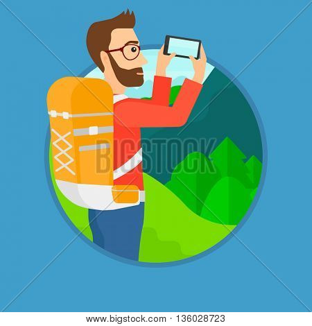 A hipster man with the beard taking photo of landscape with mountains. Young man with backpack taking photo with his cellphone. Vector flat design illustration in the circle isolated on background.