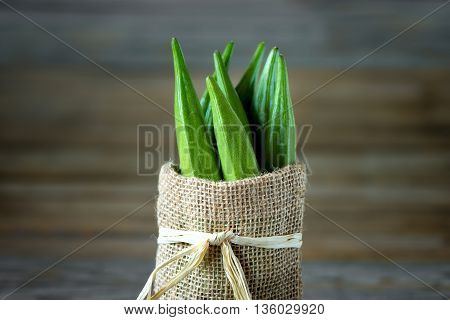 A heap of raw okra or Lady's fingers or gumbo in a bag on wooden background