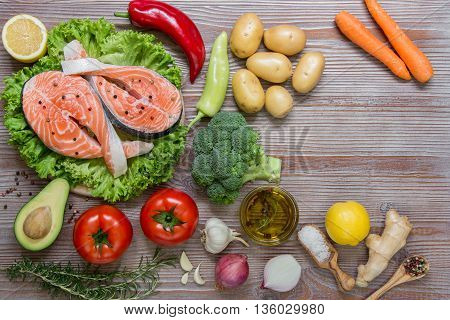 Left salmon fillets on the lettuce near summer season vegetables herb spices and olive right empty space on wood background. Salmon fillets and summer vegetable ingredients. Horizontal. Top view.