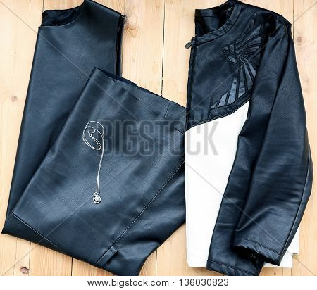 Total woman evening outfit top view of black leather dress and jacket with evening accessory