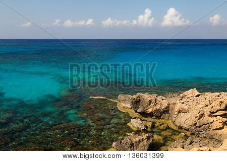Seascape with azure transparent sea and rocks in water coast of Mediterranean Sea at sunny summer day. Coast of Cyprus Ayia Napa.