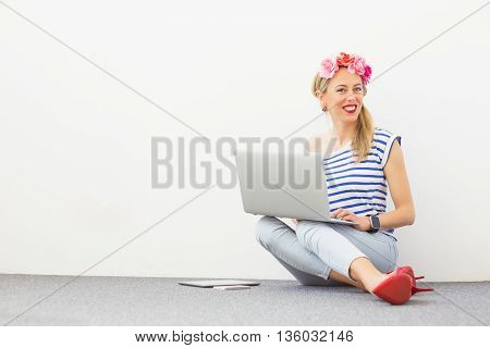 Fashion blogger sitting on the floor and using computer