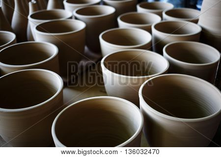 Many rustic handmade terracotta clay pots ready to be fired. Shallow depth of field. Selective focus.