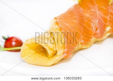 scrambled eggs with cheese and salmon decorated with tomato on white background