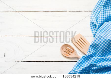 Kitchen blue plaid towel on a white wooden table. Top view with copy space