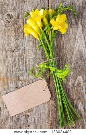 Bouquet of freesia flowers with blank tag tied with string