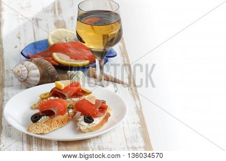 Tasty various italian sandwiches with seafood against white rustic wooden background. Crostini with cheese slices of red fish lemon olives on white plate close up with selective focus