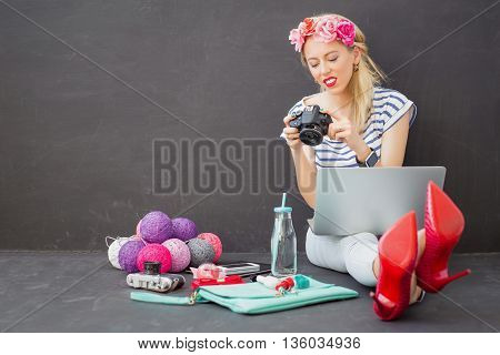 Woman with laptop in her lap looking at pictures in the camera