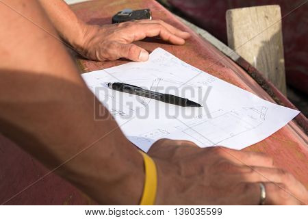 Closeup photo of drawing, pencil and hands of a carpenter who is going to make design