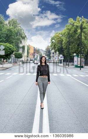 Beautiful woman walking on the median strip of the road in the city