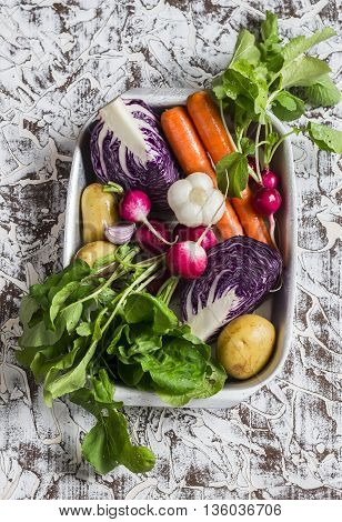 Fresh vegetables - red cabbage radishes carrots potatoes garlic onions in a metal box on a light stone background. Healthy vegetarian diet detox food. Top view