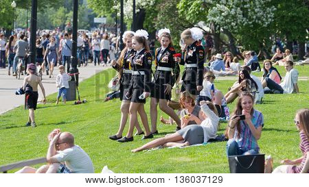Moscow - May 9 2016: People relax and four young beautiful girls in uniform are in Gorky Park on Victory Day May 9 2016 Moscow Russia